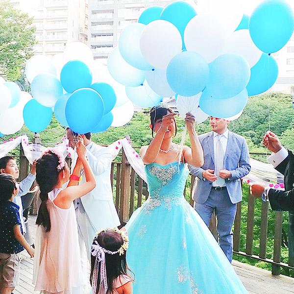 結婚式のバルーンリリースをテラスで配る新郎新婦。
