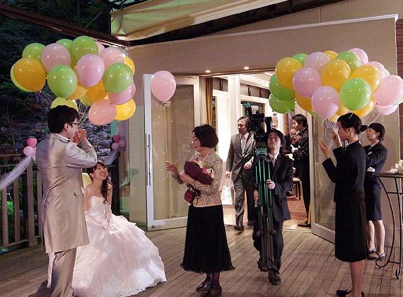 結婚式に納品されたバルーンの束のおもりを切って、ゲストに手渡ししてバルーンリリース